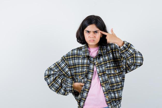 셔츠를 입은 십대 소녀, 그녀의 관자놀이를 가리키고 화난 표정을 짓고 있는 재킷.