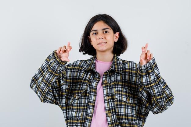 シャツを着たプレティーンの女の子、交差した指を示すジャケット、正面図。