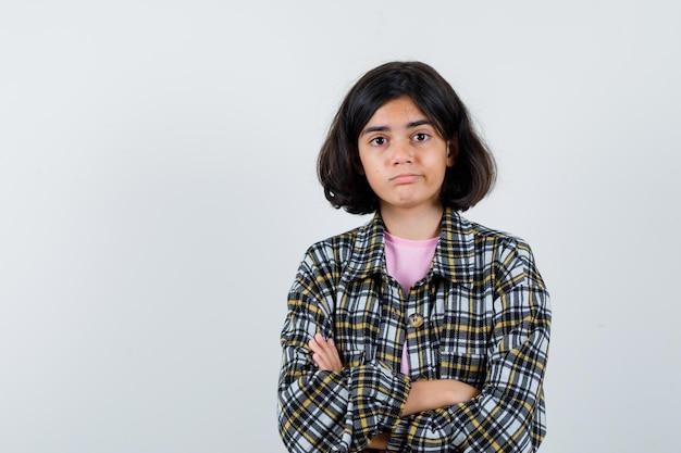 Девочка десятилетнего возраста в рубашке, куртке, стоя со скрещенными руками и растерянной, вид спереди. место для текста