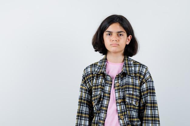 Ragazza preteen che guarda l'obbiettivo in camicia, giacca e annoiata. vista frontale. spazio per il testo