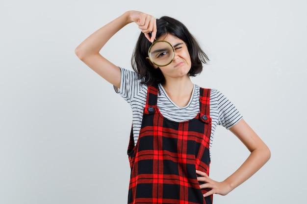 Tシャツで拡大鏡で探しているプレティーンの女の子