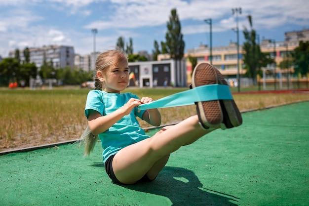 シティスポーツの公共運動場でフィットネスレジスタンスバンドでエクササイズをしているプレティーンの女の子