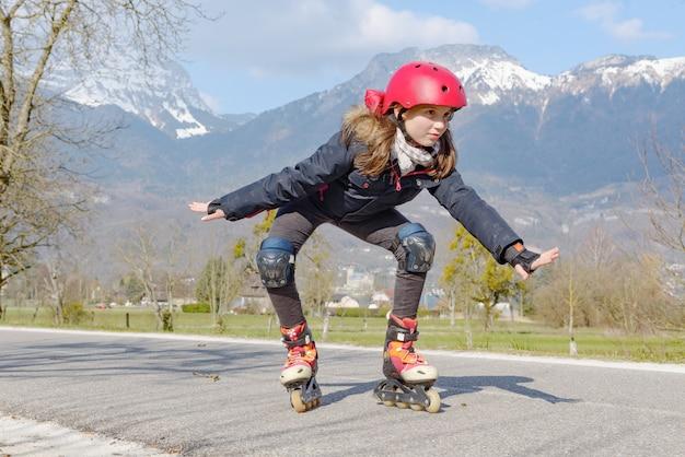 トラックでヘルメットのローラースケートのプレティーンの女の子