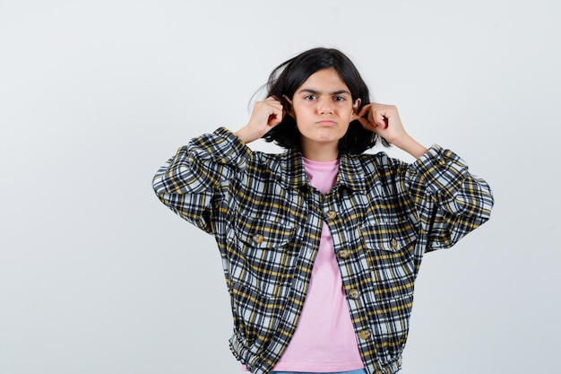 Preteen girl pinching her ears in shirt,jacket front view.