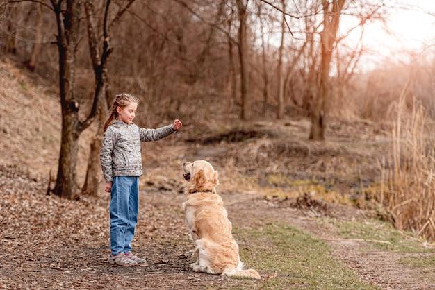 봄 날에 자연에 골든 리트리버 강아지와 함께 연주 초반 이었죠 소녀