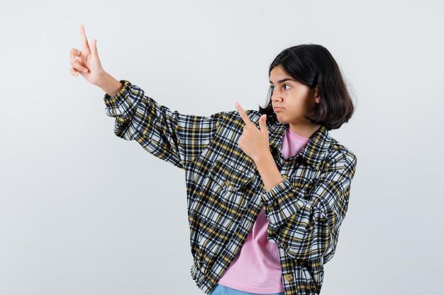 シャツ、ジャケットの正面図で脇を指しているプレティーンの女の子。