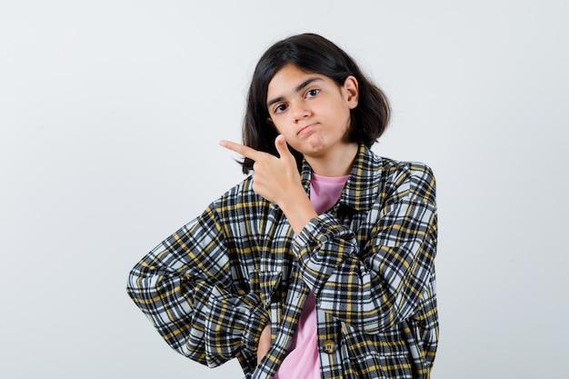 Ragazza preteen che indica da parte in camicia, giacca e sembra assicurata. vista frontale.