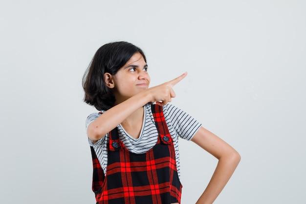 Tシャツ、ジャンプスーツを着て、気配りをしているプレティーンの女の子。 無料写真