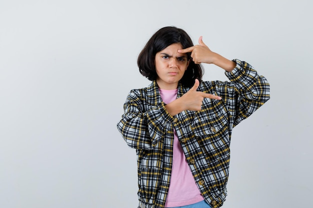 Preteen girl pointing at left and right in shirt,jacket , front view.