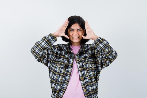 彼女の顔を見せるために手を上げて、シャツ、ジャケットで微笑んで、満足そうに見えるプレティーンの女の子。正面図。