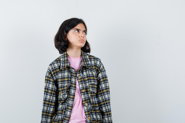 Preteen girl in shirt,jacket looking aside , front view.