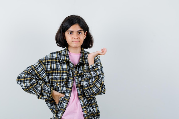 Preteen girl in shirt,jacket showing something at left and looking displeased , front view.
