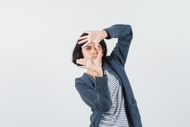 Preteen girl showing frame gesture in shirt,jacket and looking concentrated.