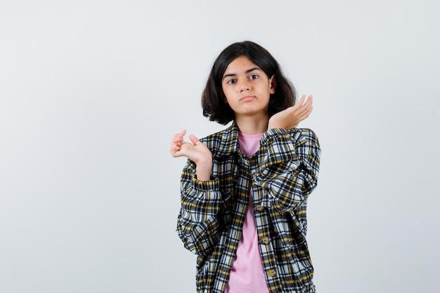 シャツ、ジャケットの正面図でジェスチャーがわからないことを示すプレティーンの女の子。