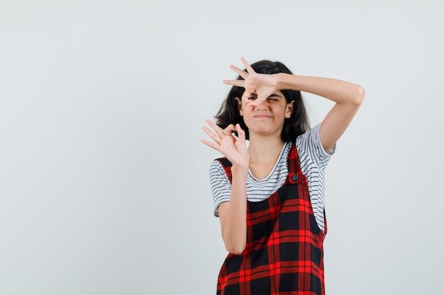Tシャツ、ジャンプスーツでokジェスチャーを示し、満足そうに見えるプレティーンの女の子