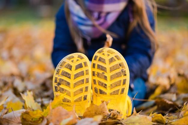 プレティーンの女の子は雨靴で秋の公園に座っています
