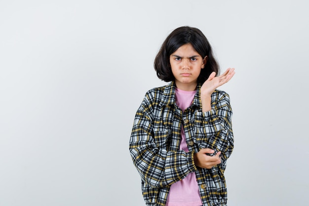 Preteen girl spreading open palm aside in shirt,jacket and looking dissatisfied. front view.