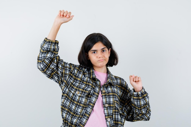 Preteen girl stretching arms in shirt,jacket and looking flexible. front view.