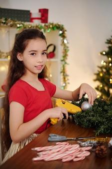 Девочка-подросток с помощью горячего клея прикрепляет фенечки к рождественскому венку