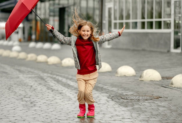 Preteen girl wearing roober boots and holding umbrella outdoors in rainy autumn day smiling. pretty child in gumboots having fun at wet street