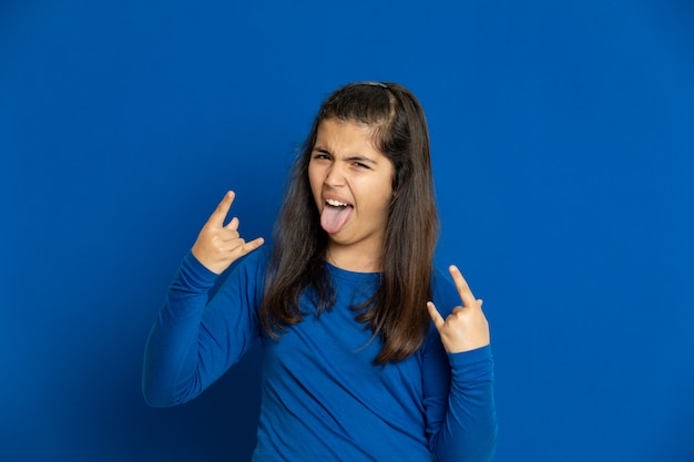 青い壁に身振りで示す青いジャージーのプレティーンの女の子