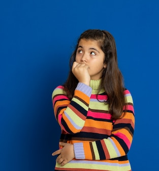 Preteen girl with striped jersey gesturing over blue wall