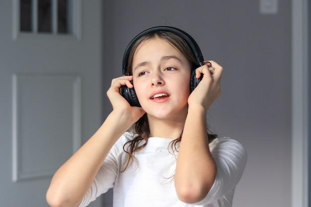 Preteen girl with wireless headphones listening to music