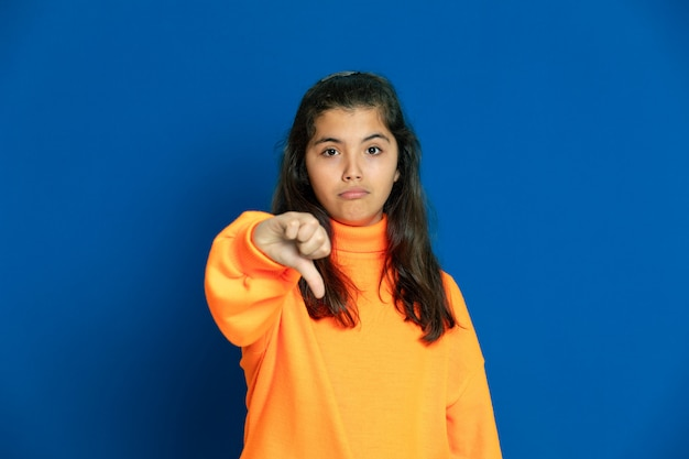 Preteen girl with yellow jersey gesturing over blue wall