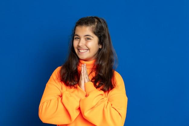 青い壁に身振りで示す黄色のジャージーのプレティーンの女の子