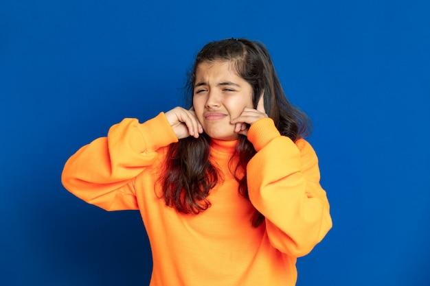 Preteen девушка с желтой майкой, указывая на синюю стену