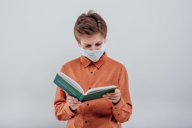 흰색 배경에 격리된 책을 읽고 의료 마스크를 쓴 초반 안전 및 학습