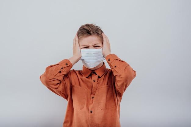 의료용 마스크를 쓴 10대 초반은 흰색 배경에 격리된 머리에 손을 얹고 두통을 앓고 있다