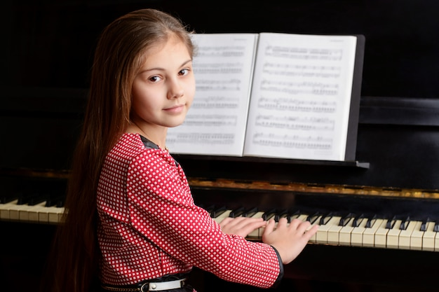 Preteen little girl musician sitting at piano