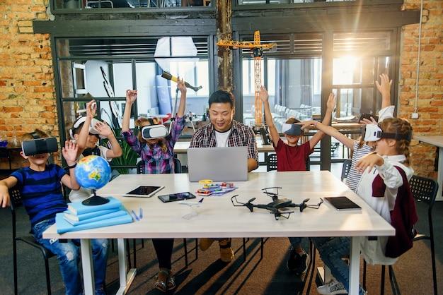 現代のスマートスクールで勉強するために拡張現実を使用しているプレティーンの学生。コンピューターサイエンスのクラス中にvrヘッドセットを持つ生徒のグループ。