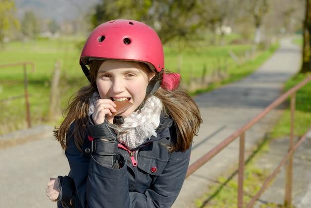 ローラースケートヘルメットとプレティーン、ケーキを食べる