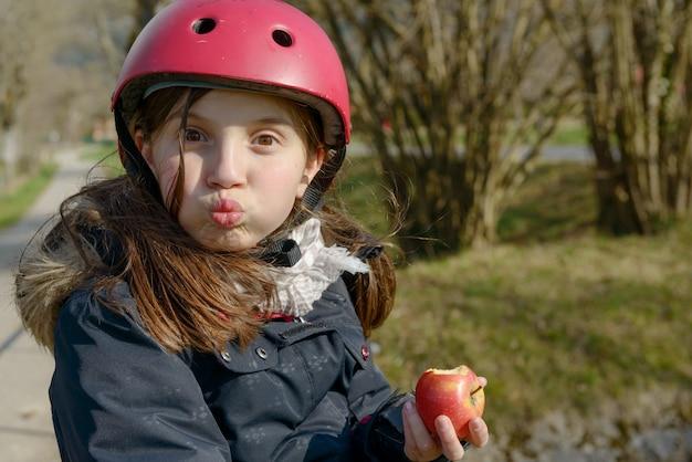 ローラースケートヘルメットとプレティーン、リンゴを食べる