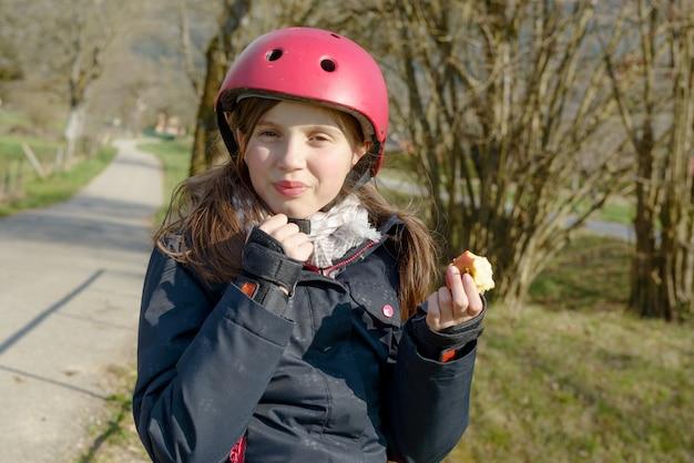 ローラースケートヘルメットのプレティーン、りんごを食べる