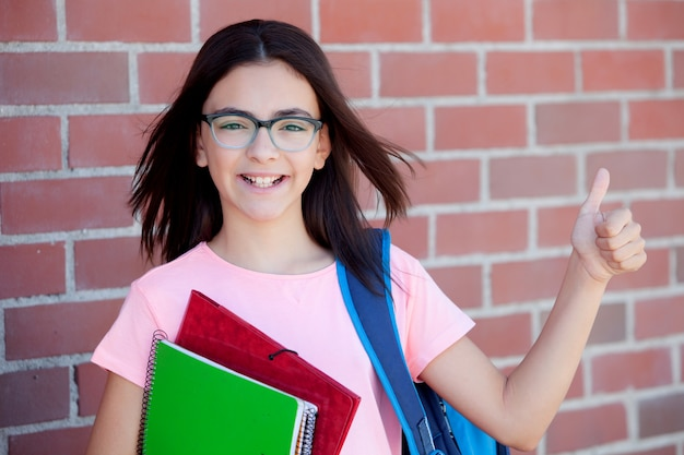 Preteenager girl next to a red brick wall with the backpack and books saying ok