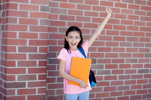 Preteenager girl next to a red brick wall with the backpack and books