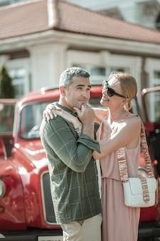 생각하는 척. 그의 아름다운 웃는 아내의 팔에 그의 턱에 그의 손으로 서 있는 사려깊은 남자.