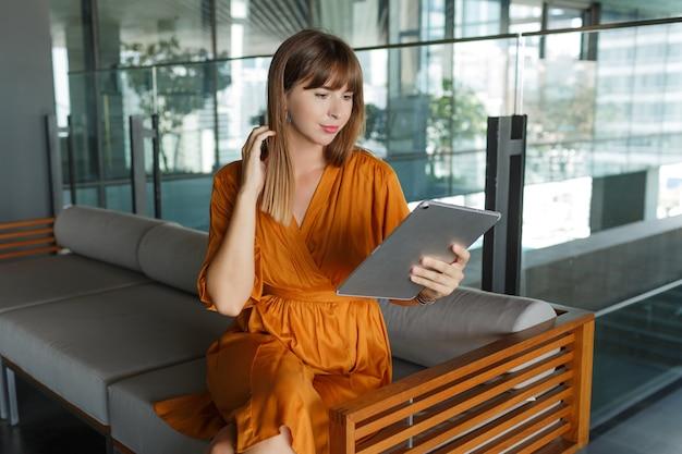 Bella donna europea utilizzando tablet in casa moderna, seduto sul divano.