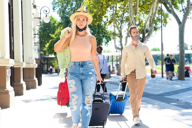 Pretti girl and boy walking in front of the train station with the face mask -  couple walks with luggage - new normal travel and lifestyle concept