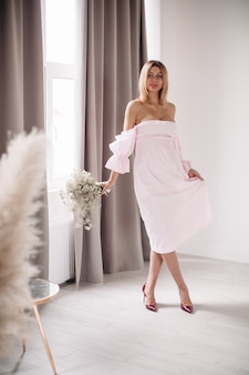 大きな窓の近くに立って花を持っている白いドレスを着たprettu白人女性