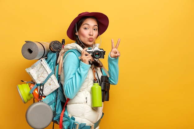 Pretty active backpacker makes victory gesture, keeps lips rounded, holds retro camera, stands with travelbag, takes photos during trip, isolated over yellow background