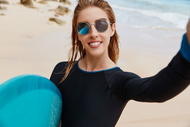 Pretty active female in sunglasses poses for selfie and makes photo at beach, carries blue surfboard, happy to spend free time with favourite hobby. people, lifestyle, surfing and recreation concept