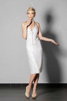 Pretty actress in pearl white retro dress dancing charleston