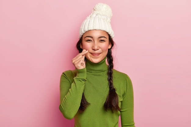 Pretty adorable girl makes korean heart gesture, has long hair combed in plaits, wears warm knitted hat and casual turtleneck, has natural beauty, isolated over pink studio wall