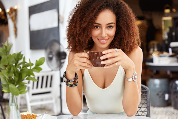 Pretty adorable woman has curly hair wears casual clothing, keeps cup in hands with aromatic coffee, sits against cozy restaurant, has break after work.