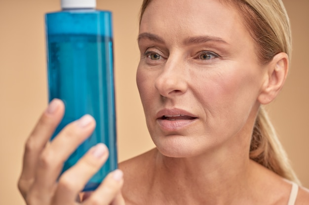 Pretty adult lady going to use antiaging lotion