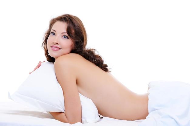 Довольно взрослая обнаженная девушка лежит на кровати и обнимает подушку
